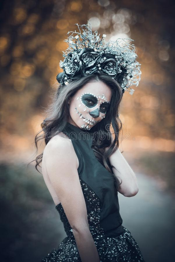 Closeup portrait of Calavera Catrina in black dress. Sugar skull makeup. Dia de los muertos. Day of The Dead. Halloween. Mexican, party, mexico, background royalty free stock photo