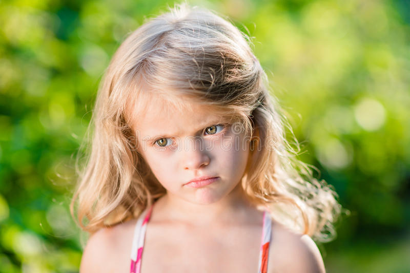 Closeup portrait of capricious blond little girl with pursed lips. Close-up portrait of capricious blond little girl with pursed lips. Sunny summer day in stock image