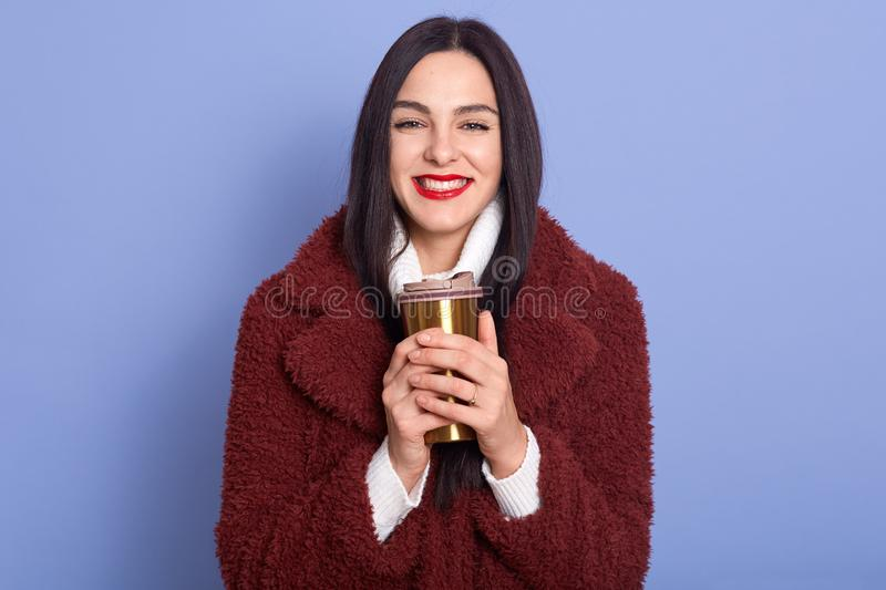 Closeup portrait of charismatic beautiful woman smiling sincerely, having red lips, holding thermo mug with hot drink in both royalty free stock photos