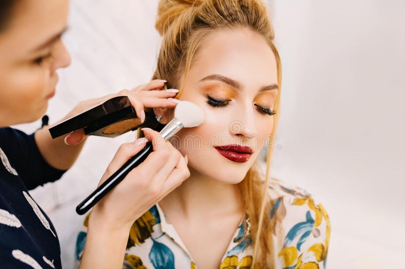 Closeup portrait charming blonde woman preparing to celebration, party in beauty salon. Making makeup, professional royalty free stock photo