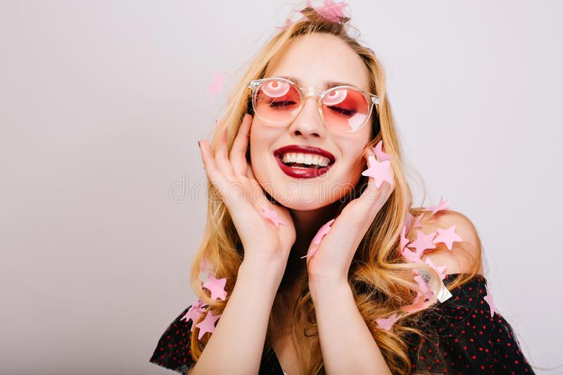 Closeup portrait of cheerful blonde woman wearing pink glasses and smiling, having fun at party, enjoying with closed. Eyes. Has long curly hair, stylish look stock photo