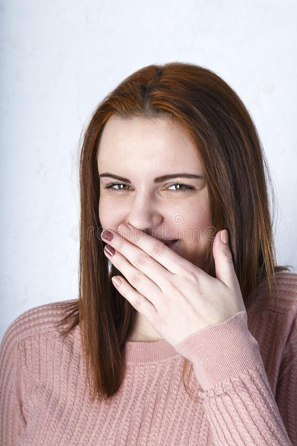 Closeup portrait cheerful girl with beautiful face and attractive amile. Smiling shy woman covering mouth her face with a hand royalty free stock photos