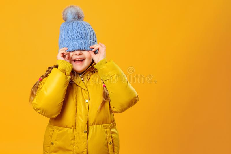 Closeup portrait of a cheerful little girl in jacket over yellow background. The child hides his eyes under the cap stock images