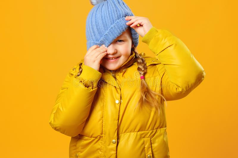 Closeup portrait of a cheerful little girl in jacket over yellow background. The child looks out from under the hat stock photos