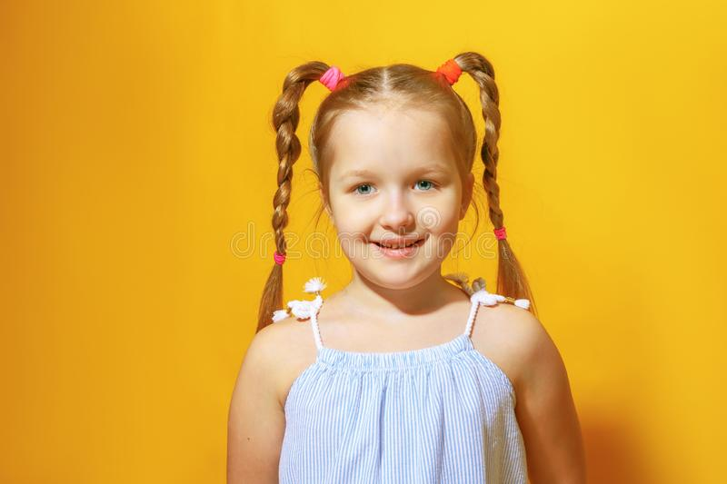 A closeup portrait of a cheerful little girl with pigtails out of her hair against a yellow background. royalty free stock photo