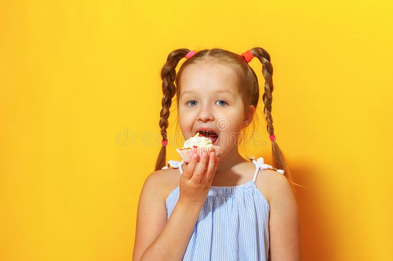 Closeup portrait of a cheerful little girl on a yellow background. A child with braids of hair bites cake stock image