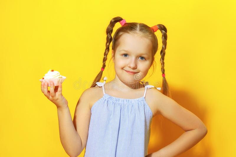 Closeup portrait of a cheerful little girl on a yellow background. A child with pigtails of hair holding a cake in his hands royalty free stock image