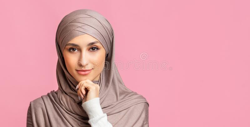 Portrait of confident islamic woman in headscarf posing over pink background stock photo