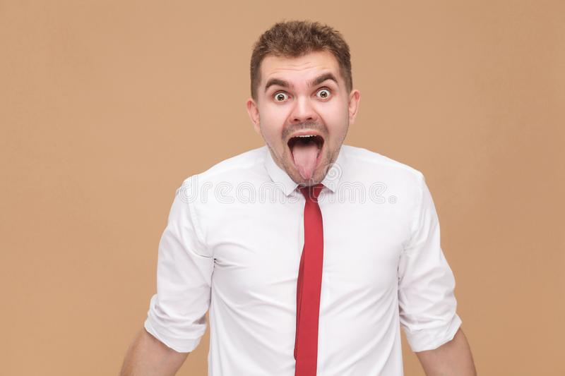 Closeup portrait of crazy businessman showing tongue out. Business people concept, good and bad emotion and feelings. Studio shot, on light brown background royalty free stock image