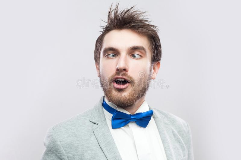 Closeup portrait of crazy funny handsome bearded man in casual grey suit and blue bow tie standing with crossed eyes and looking royalty free stock images