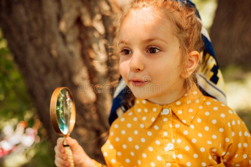 Closeup portrait of curious little girl playing with magnifying glass, exploring the nature outdoor. Adorable little kid explorer. Playing and looking through royalty free stock images