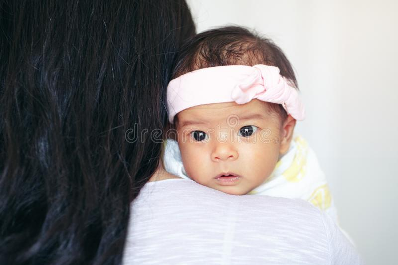 Closeup portrait of cute adorable awake Asian Chinese mixed race newborn baby girl with open eyes lying on parent shoulder royalty free stock image