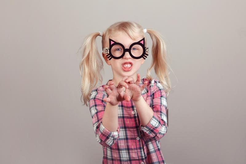 Caucasian preschool girl wearing funny cat glasses. Closeup portrait of cute adorable blonde Caucasian preschool girl wearing funny cat glasses and playing stock images