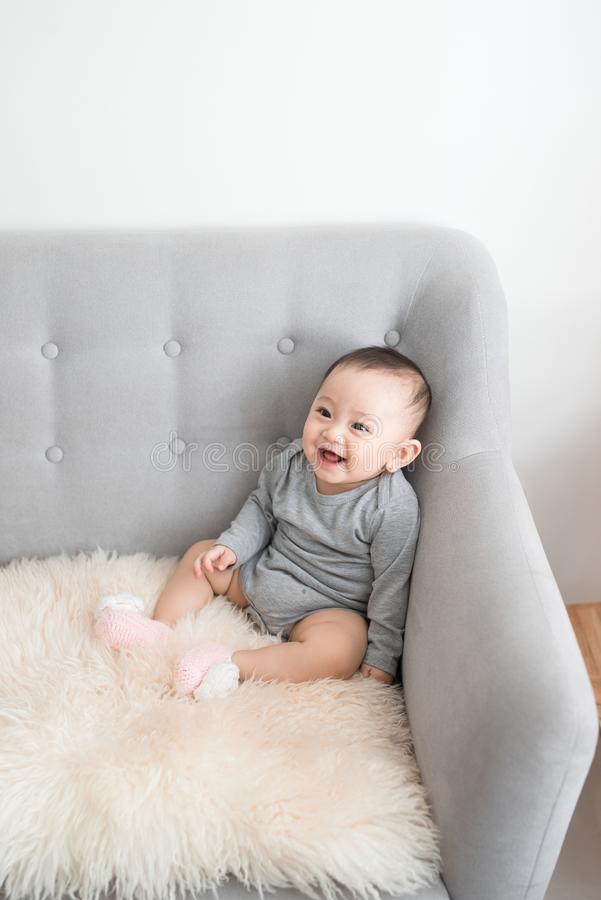 Closeup portrait of cute adorable smiling laughing, baby girl with black eyes sitting on sofa looking away from camera, natural. Window light, lifestyle royalty free stock photo