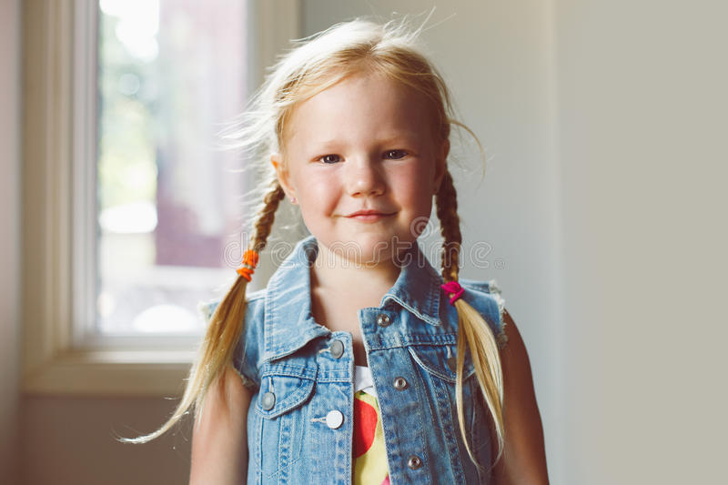 Cute adorable white blonde Caucasian smiling girl looking in camera. Closeup portrait of cute adorable white blonde Caucasian smiling girl looking in camera royalty free stock photography