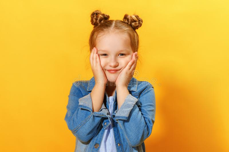 Closeup portrait of a cute attractive little girl on yellow background. Child hands face and looks into the camera.  royalty free stock photos
