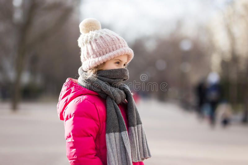 Closeup portrait of cute baby girl wearing knitted hat and winter jacket outdoors stock photo