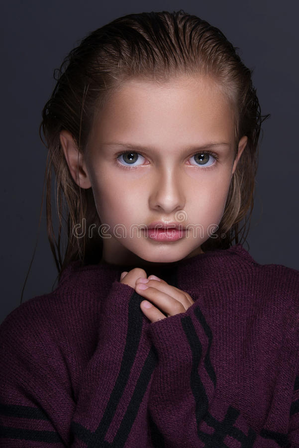 Closeup portrait of cute little girl with dark hair in studio over grey background. royalty free stock images