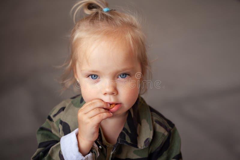 Closeup portrait cute little girl eating cookie stock photo