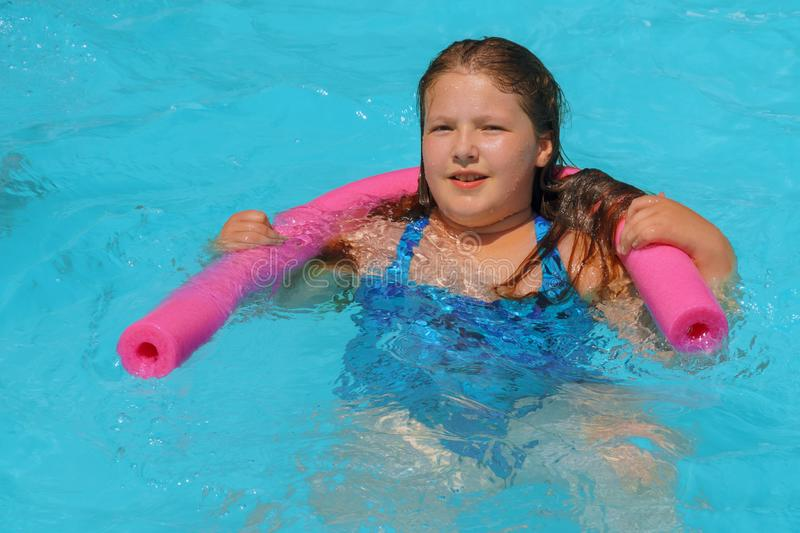 Closeup portrait of cute little girl swimming in the pool, happy child having fun in water summer vacation holidays royalty free stock image
