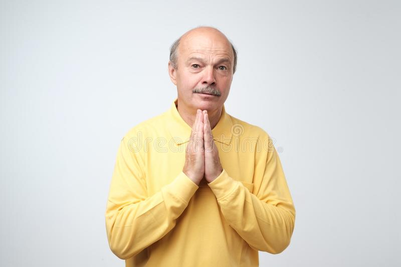 Closeup portrait of desperate mature man in yellow shirt showing clasped hands,asking for help or excuse. stock photography