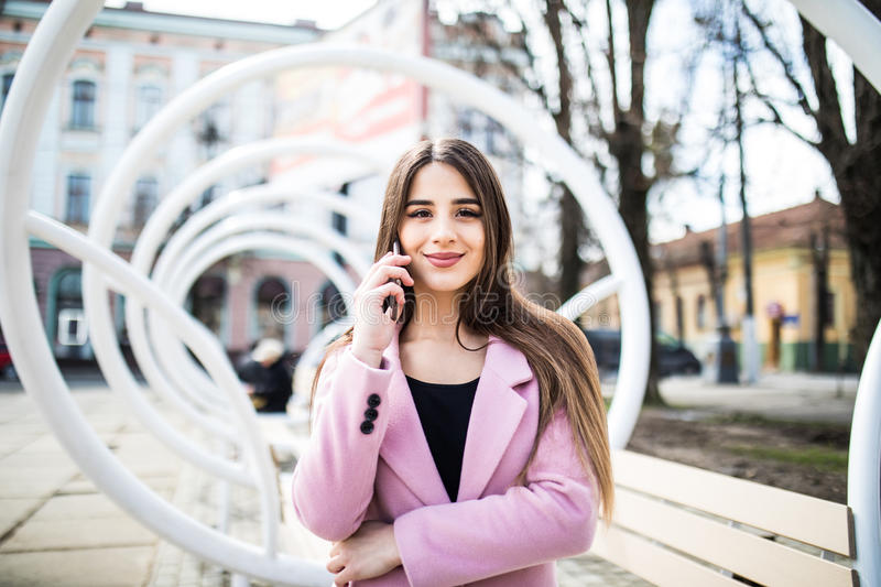 Closeup portrait of enjoyed brunette girl speaking on phone on street. She wears pink jacket, smiling to camera royalty free stock images