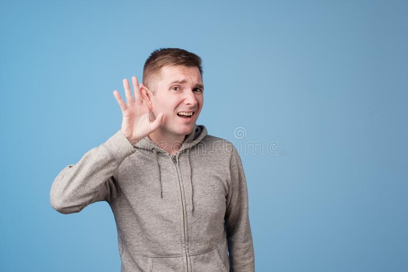 Closeup portrait of european man placing hand on ear listening carefully to gossip isolated on colored blue background. Closeup portrait of european man in grey royalty free stock photo