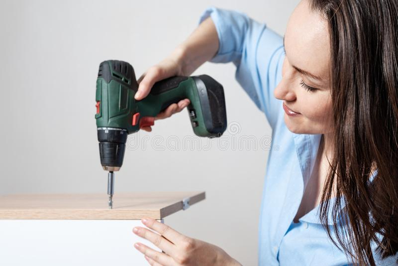 Closeup portrait of a European woman with a screwdriver in hand, collects furniture stock image