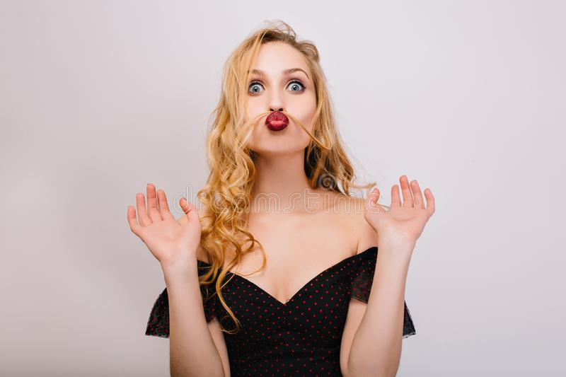 Closeup portrait of funny blonde girl being crazy, having fun, making faces, imitating moustache with hair. She has stock photos
