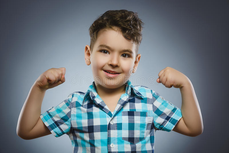 Closeup Portrait of Funny child. Strong kid showing his hand biceps muscles royalty free stock photos