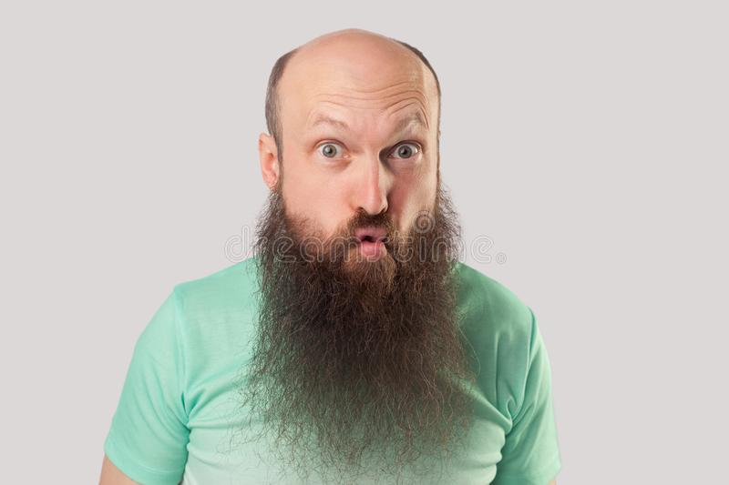 Closeup portrait of funny crazy middle aged bald man with long beard in light green t-shirt standing with big eyes and fish lips stock photos