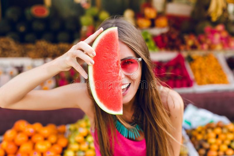 Closeup portrait of funny girl in pink sunglasses holding slice of watermelon on half face on tropical fruits background royalty free stock photo