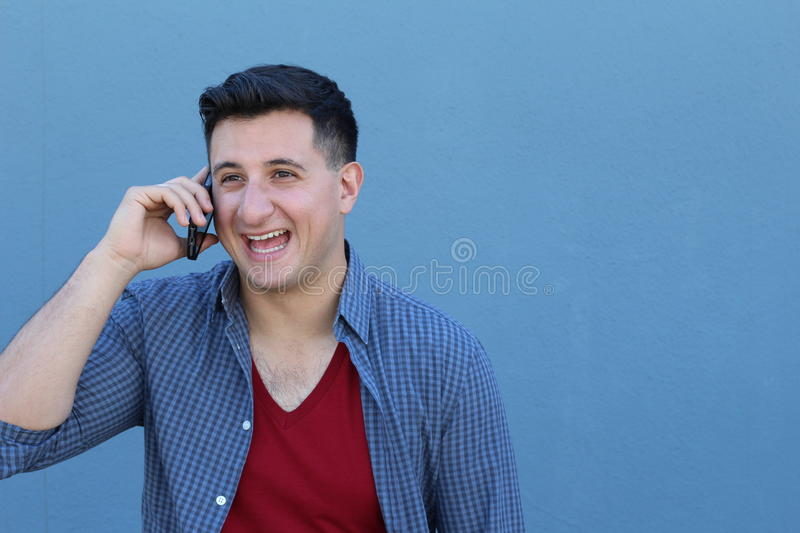 Closeup portrait, funny young man, shocked surprised, wide open mouth, large eyes by what he listens on his cell phone,. On blue background stock images