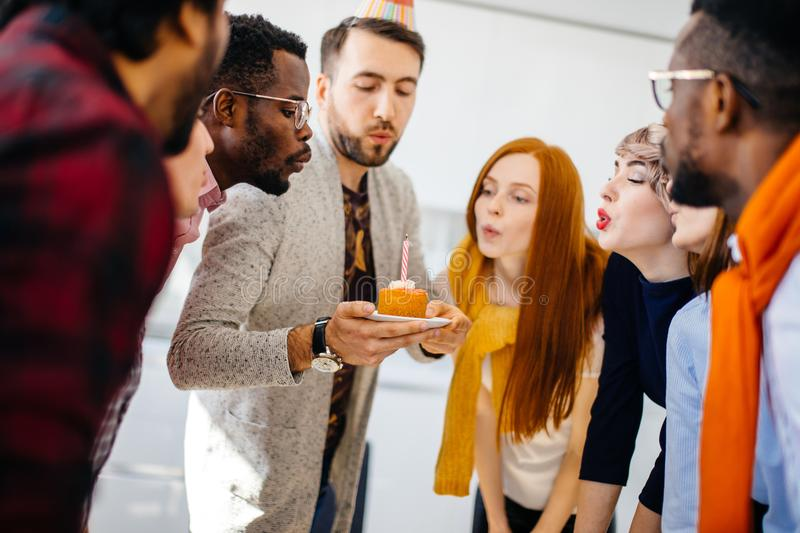 Closeup portrait of good-looking guy holding a peace of cake royalty free stock photography
