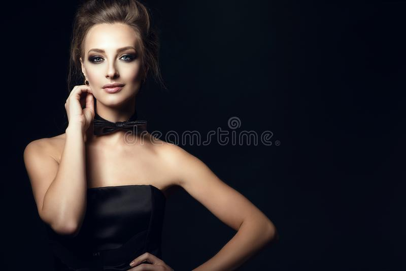 Gorgeous glam woman with beautiful make up and updo hair wearing black corset dress and bow tie on her neck royalty free stock photo