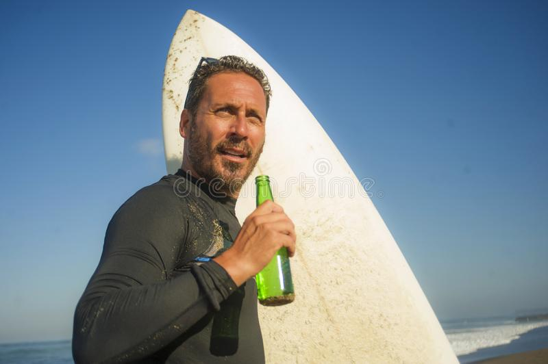 Attractive surfer man in neoprene swimsuit holding surf board posing cool and happy after surfing enjoying Summer water sport and stock photos