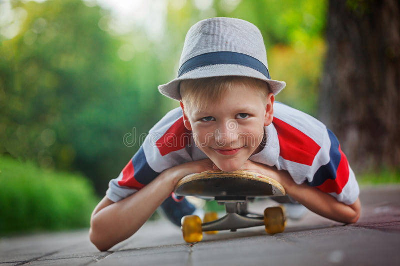 Closeup portrait handsome boy in hat lying on skateboard in sum royalty free stock photo