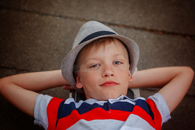 Closeup portrait handsome boy in hat lying on skateboard in summer stock photography