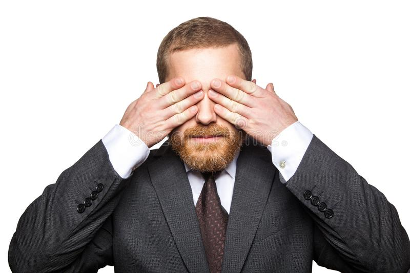 Closeup portrait of handsome businessman with facial beard in black suit standing and closed his eyes and dont want to looking stock photos