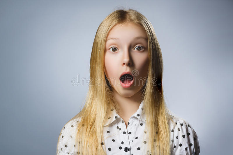 Closeup Portrait of handsome girl with astonished expression while standing against grey background royalty free stock photography