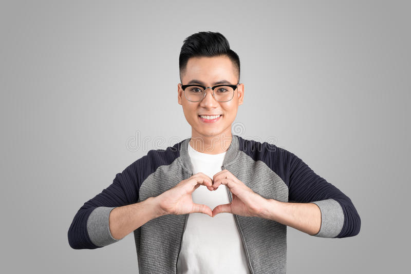 Closeup portrait handsome smiling young business man makes the heart using fingers, hands, isolated grey wall background. Positive royalty free stock photography