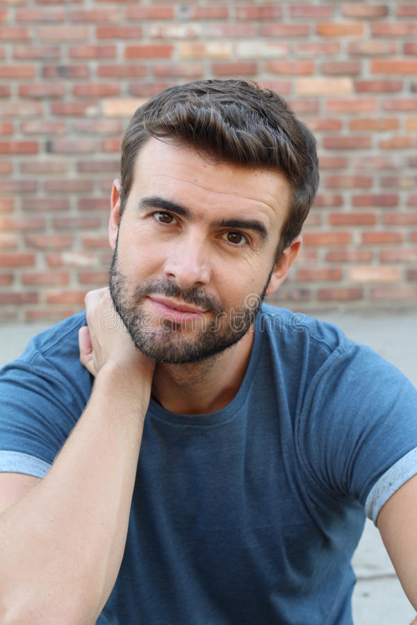 Closeup portrait of handsome young with a beard thinking deeply with finger on temple looking at you. Human face expressionss royalty free stock photos