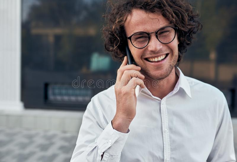 Closeup portrait of handsome young smiling businessman making a phone call while walking outdoors wearing white shirt and round stock photography