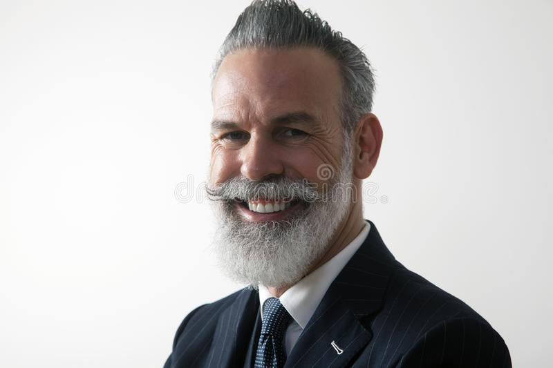 Closeup portrait of happy bearded middle aged gentleman wearing trendy suit over empty white background. Studio shot stock photos