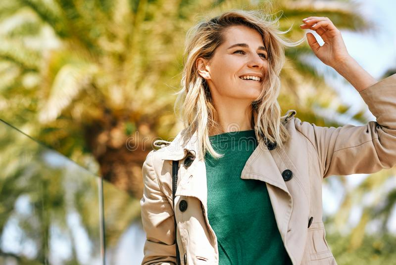 Closeup portrait of happy beautiful blonde woman smiling and enjoying the journey on the city street on sunny day, against palms stock photo