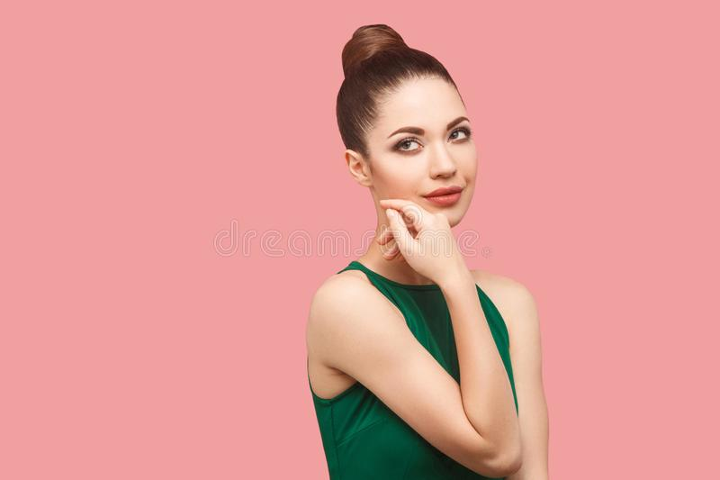 Closeup portrait of happy beautiful young woman with bun hairstyle and makeup in green dress standing touching her face and stock photos