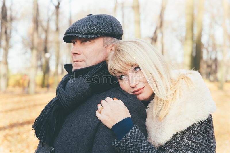 Closeup portrait of happy blonde mature woman and beautiful middle-aged brunette, looking away. Loving couple of 45-50 years old stock images