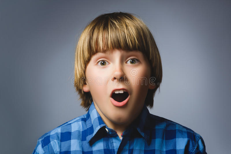 Closeup Portrait of happy boy going surprise on gray background royalty free stock image