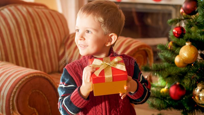 Closeup portrait of happy cheerful smiling little boy with red Christmas gift tied by golden ribbon bow royalty free stock photography