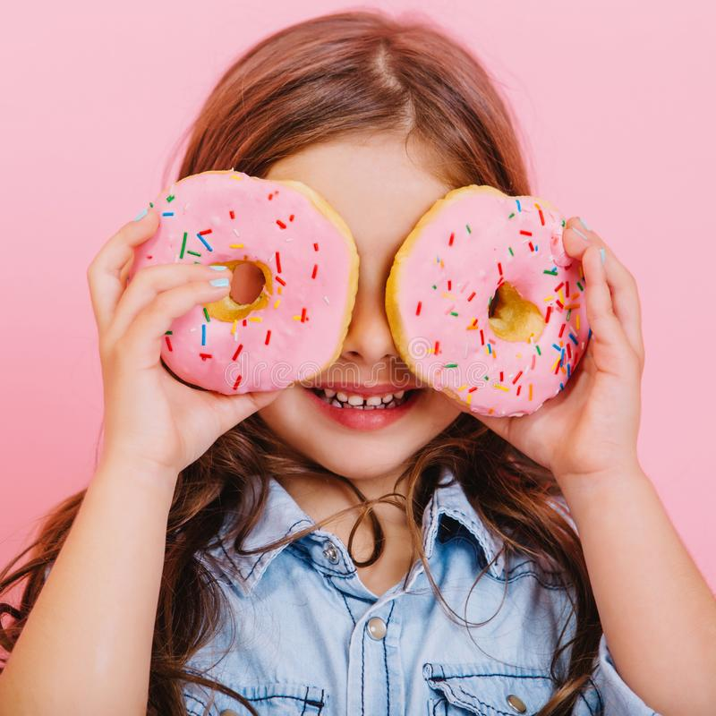 Closeup portrait happy cute little girl in blue shirt holding donuts on eyes, having fun to camera isolated on pink stock photos
